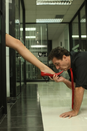 Businessman kissing womans foot photo