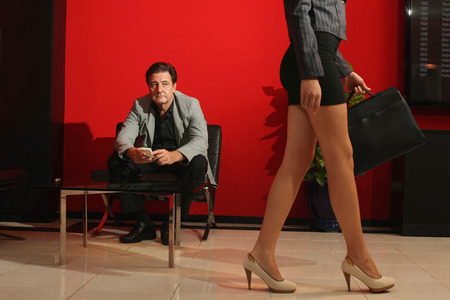 Businessman looking at businesswomans legs photo