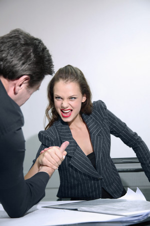 Businessman and businesswoman arm wrestling on table photo