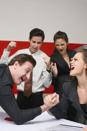 Businessman and businesswoman arm wrestling on table, the others cheering photo