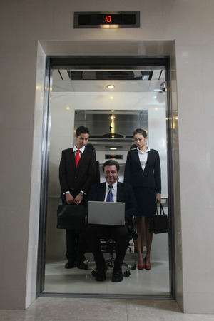 Business people watching businessman sitting on office chair and using laptop in an elevator photo