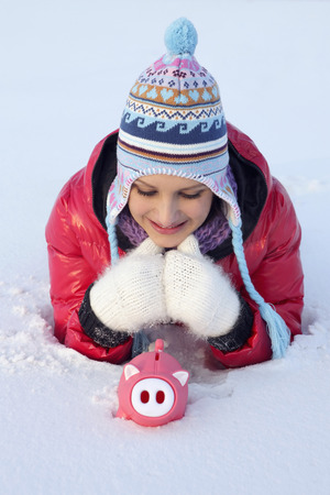 lying forward: Woman lying down and looking at piggy bank