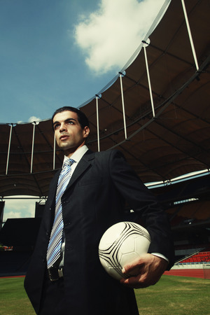 Businessman holding soccer ball photo