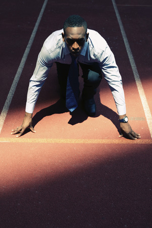 afro arab: Businessman crouching on starting line