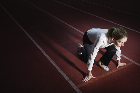 Businesswoman crouching on starting line