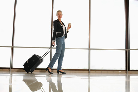 Businesswoman holding a cup of coffee while pulling her luggage photo