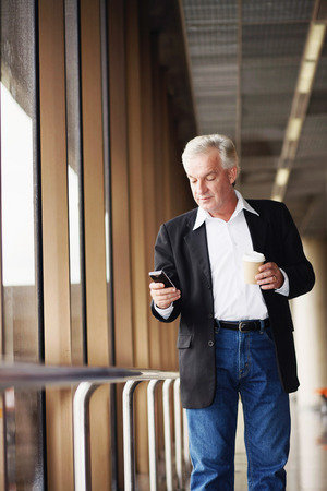 Businessman holding a cup of coffee while text messaging on phone photo