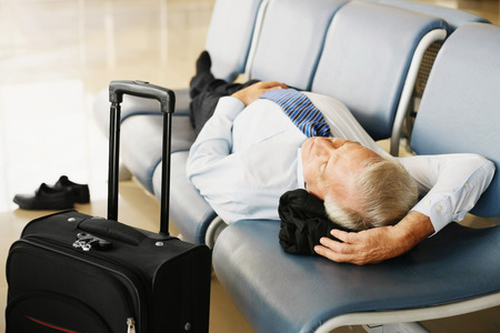 airport lounge: Businessman asleep on seat in airport lounge Stock Photo