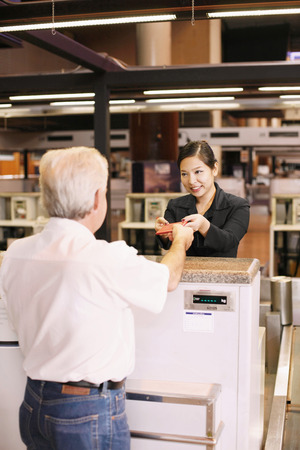 returning: Airline check-in attendant returning businessmans passport at the airport check-in counter