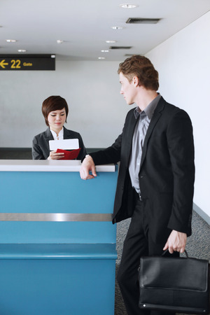 airport check in counter: Airline check-in attendant checking businessmans passport at the airport check-in counter Stock Photo