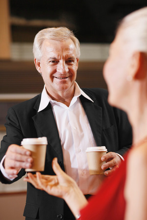 Businessman handing businesswoman a cup of coffee photo