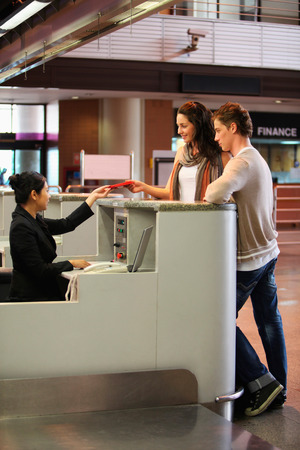 southern european descent: Man and woman at the airport check-in counter with their passports