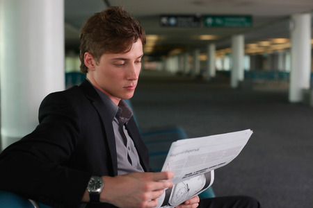 airport lounge: Businessman reading newspaper in airport lounge Stock Photo