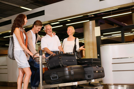 southern european descent: Family arriving at the airport of their destination, pushing luggage trolleys