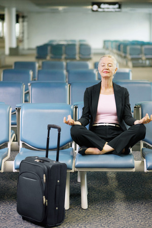 airport lounge: Businesswoman meditating in airport lounge Stock Photo