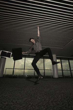 airport lounge: Businessman jumping with fist raised in airport lounge