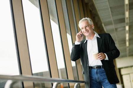 Businessman holding a cup of coffee while talking on the phone photo