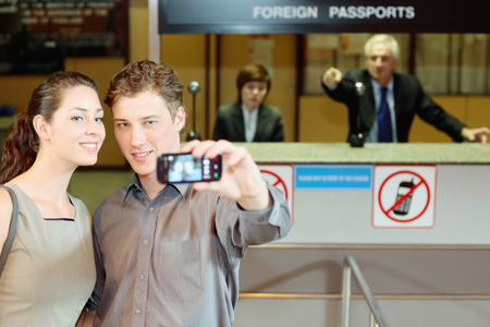 western attire: Businessman taking a picture using mobile phone, airline check-in attendant pointing at them Stock Photo