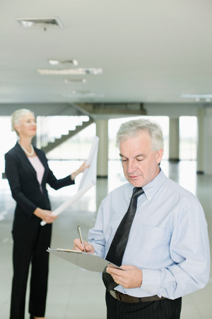 writing western: Businesswoman looking at blueprint, businessman writing on clipboard Stock Photo