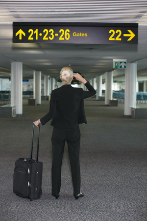 Businesswoman looking at directional sign in airport lounge photo
