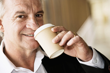 Businessman drinking coffee while waiting in airport lounge photo