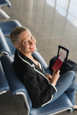 airport lounge: Businesswoman sitting in airport lounge holding her passport Stock Photo