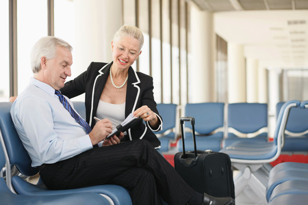 airport lounge: Businessman writing in organizer, businesswoman sitting beside him in airport lounge Stock Photo