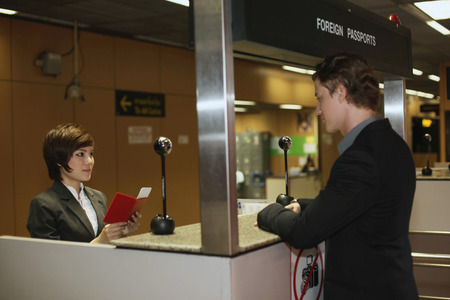 Airline check-in attendant checking businessmans passport at the airport check-in counter photo