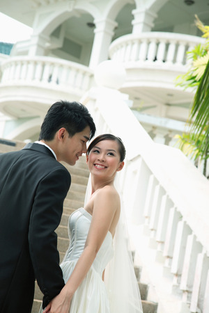 Bride and groom posing on stairway photo