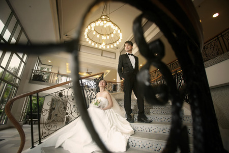 Bride and groom posing indoors on the stairway photo