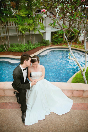 Bride and groom sitting on the edge of bride over the swimming pool photo