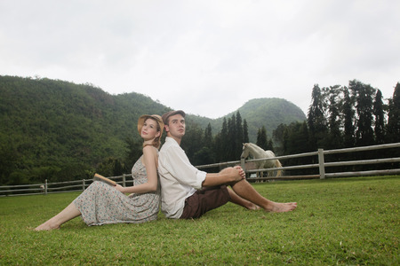 Man and woman sitting on grass photo