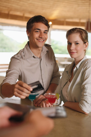 central european ethnicity: Man and woman drinking at the bar, man paying for the drinks Stock Photo