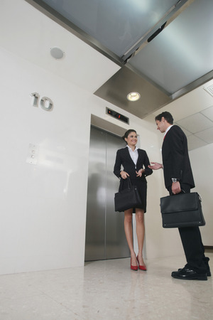 Businessman and businesswoman chatting while waiting for elevator