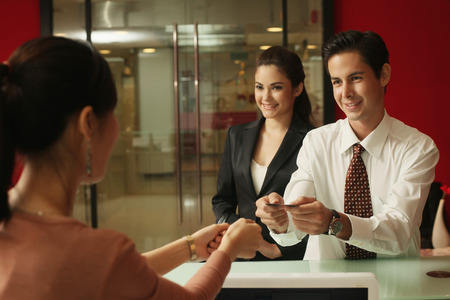 Business people passing business card to receptionist photo