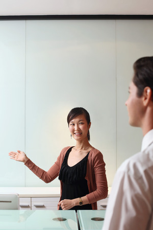 Receptionist greeting businessman photo