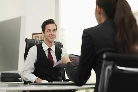Businesswoman passing document to businessman photo