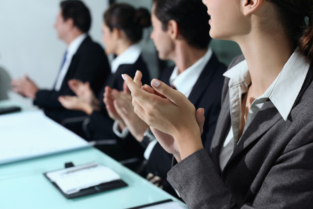Business people clapping hands at meeting photo