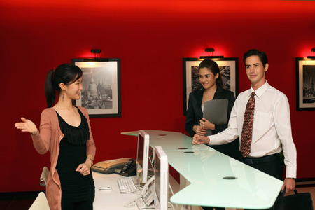 Receptionist greeting business people photo