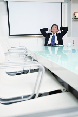 Businessman sitting on office chair with hands behind head photo