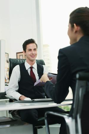 Businesswoman passing document to businessman Imagens