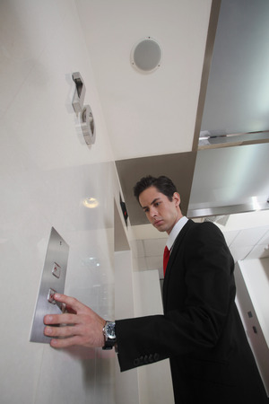 Businessman pushing elevator button photo