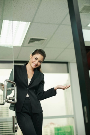 Businesswoman opening office door with a welcoming gesture