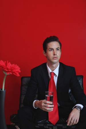 Businessman with a glass of water sitting on sofa photo