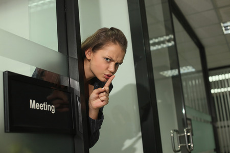 Businesswoman with finger on lips photo