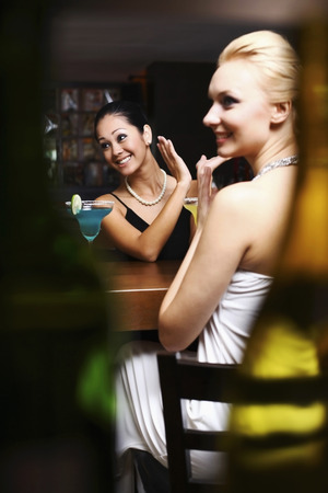 Women applauding and laughing in a bar photo
