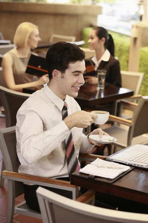 Businessman drinking coffee while looking at laptop, businesswomen sitting in the background photo