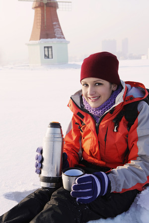 Woman enjoying hot drink on winter day photo