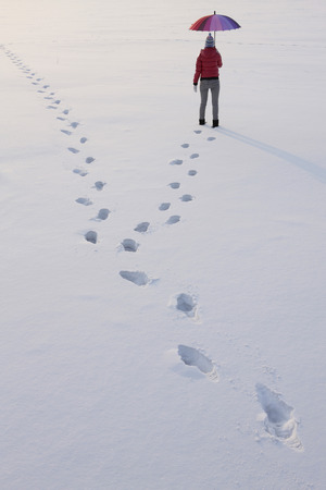 Footprints of woman walking on snow photo
