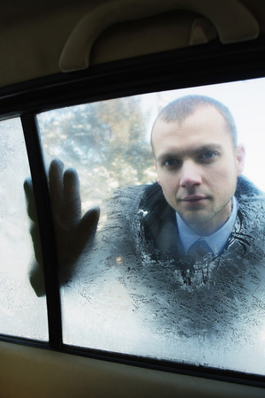Businessman wiping the fogged window photo